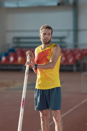 Pole vaulting indoors - a man in yellow shirt standing on the track with a pole - sports stadium