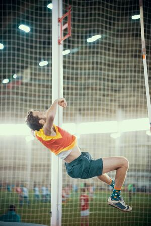 Pole vaulting indoors - an athletic man falling down after the jump - bright lights on the background