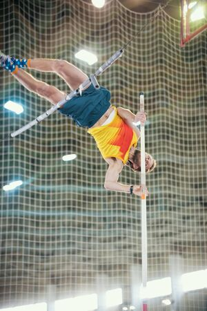 Pole vaulting indoors - a sportive man jumping over the bar - leaning on the pole