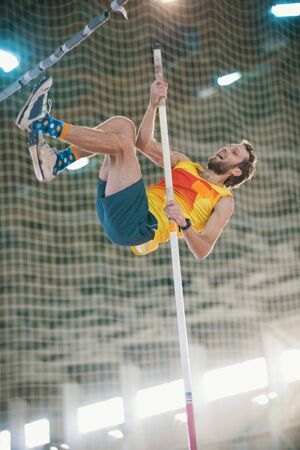 Pole vaulting in the sports stadium - an athletic man jumping over the bar