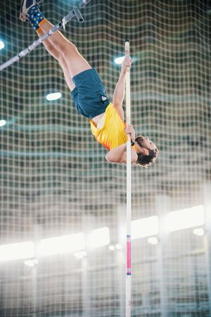 Pole vaulting - a athletic man jumping over the bar - leaning on the pole Banco de Imagens
