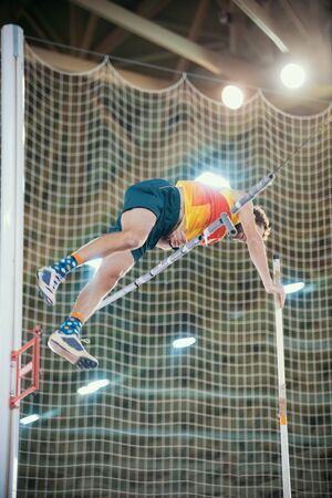 Pole vaulting indoors - a sportive man jumping over the bar - leaning on the pole - bright lights on the background