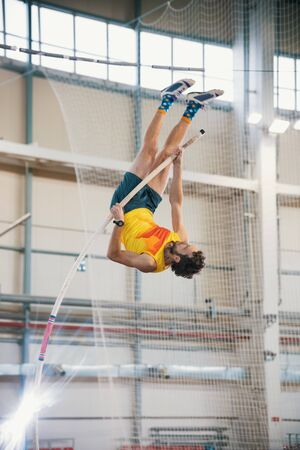 Pole vaulting indoors - a athletic man jumping over the bar - leaning on the pole