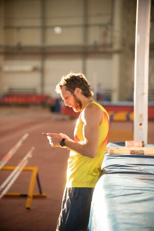 A man in yellow shirt standing on the sports stadium holding a phone