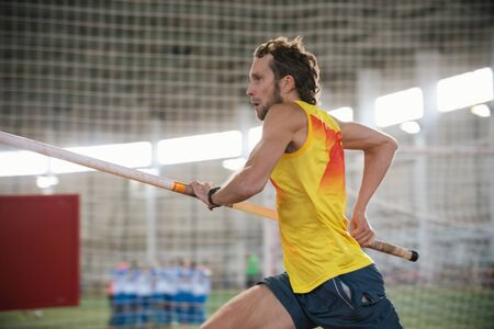 Pole vaulting indoors - a athletic man running on the track with a pole in the stadium - running up for the jump