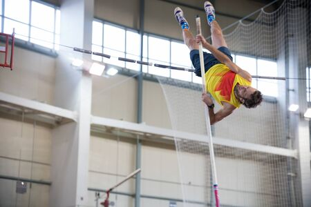 Pole vaulting indoors - a athletic man jumping over the bar Banco de Imagens