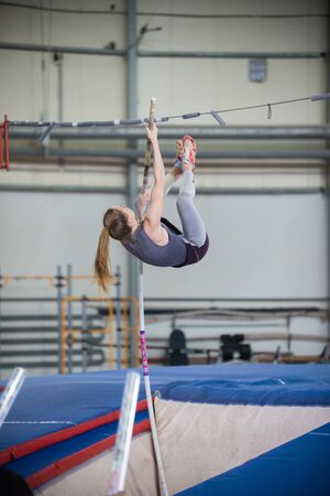 Pole vaulting - young woman is jumping over the high bar