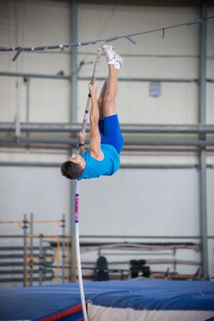 Pole vaulting - man is pushing the pole against the floor and reaching for the bar Banco de Imagens