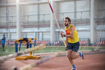 Pole vaulting - man in blue shorts is running with pole in hands