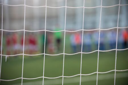 A football field - white soccer net and players on the background