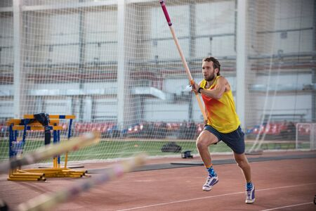 Pole vaulting indoors - a athletic man in yellow shirt running on the track with a pole in the stadium - running up for the jump