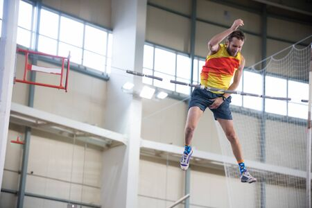 Pole vaulting indoors - a athletic man jumping over the bar and trying not to touch the bar Banco de Imagens