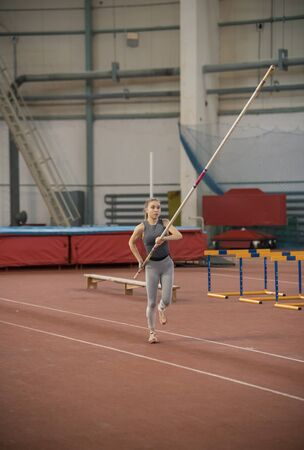 Pole vaulting in the sports stadium - young sportive woman with ponytail in grey leggins running with a pole Banco de Imagens