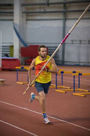 Pole vaulting - man in yellow shirt is running with a pole in hands Reklamní fotografie