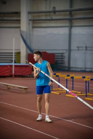 Pole vaulting - a young guy is standing with a pole in hand