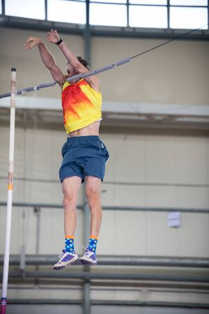 Pole vaulting indoors - a man falling down after jumping over the bar Banco de Imagens