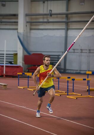 Pole vaulting indoors - a man in yellow shirt running on the track with a pole in the stadium Stockfoto