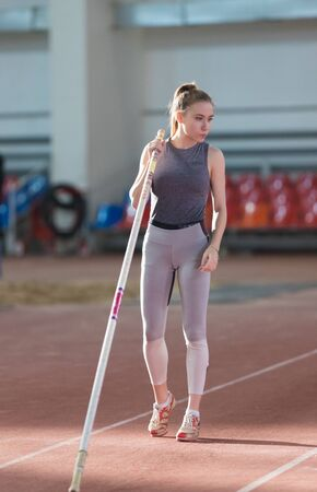Pole vaulting - woman in gray leggings is standing with pole