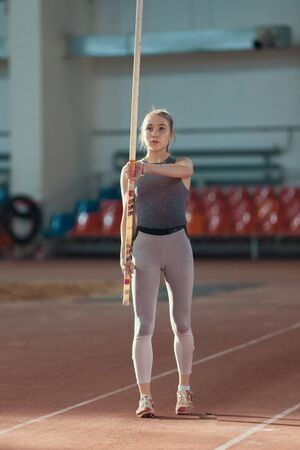 Pole vaulting - woman in gray leggings is rising a pole up