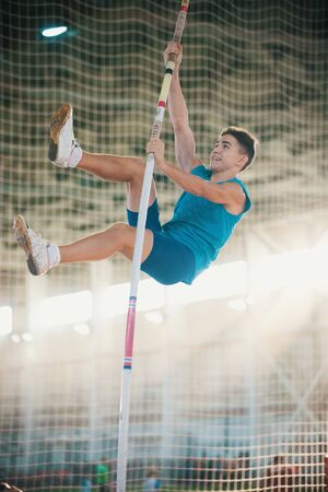Pole vaulting - man is holding the pole by his hands