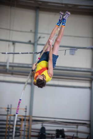 Pole vaulting indoors - a man jumping over the bar