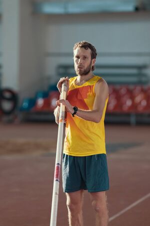 Pole vaulting - man with a beard in yellow shirt is standing with a pole Reklamní fotografie