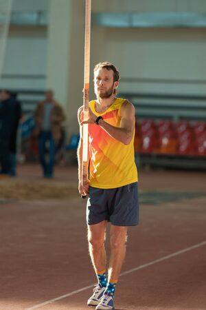Pole vaulting - man with beard is holding a long pole in yellow t shirt