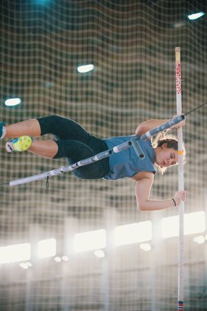 Pole vaulting - young woman in purple shirt is landing while leaning on a pole