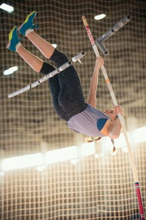 Pole vaulting - young woman in purple shirt is falling after jump Reklamní fotografie