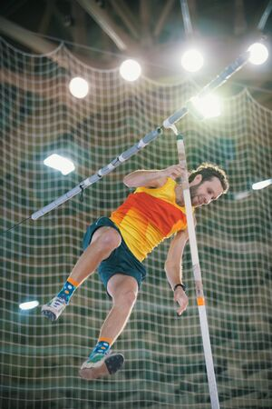 Pole vaulting - man in yellow t shirt is falling after a jump with a pole and smiling Reklamní fotografie