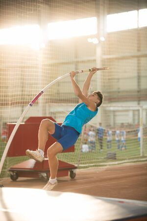 Pole vaulting - man is pushing the pole against the floor and starting his jump