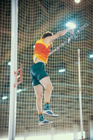 Pole vaulting - man in yellow t shirt is falling after jump with pole