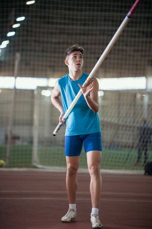 Pole vaulting - young guy in a blue suit is rising in hands a pole