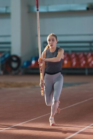 Pole vaulting - woman in gray leggings is running with a pole in her hands Reklamní fotografie