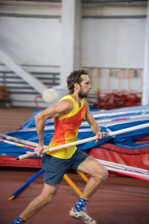 Pole vaulting - man is running with pole in hands Stockfoto