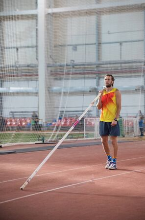 Pole vaulting - man with a beard is standing with a pole