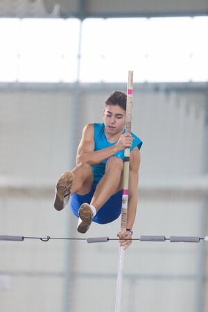 Pole vaulting - guy in a blue t shirt is jumping over the bar Stockfoto