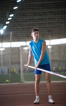 Pole vaulting - young guy in a blue suit is holding a pole