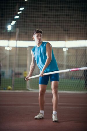 Pole vaulting - young guy in a blue suit is standing with a pole in hands