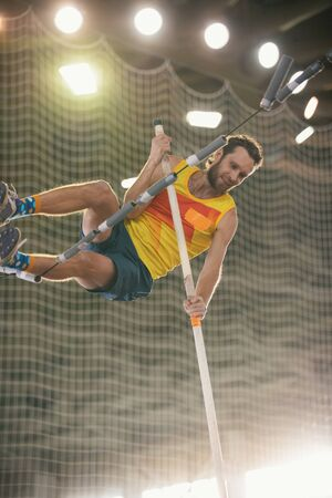 Pole vaulting - guy in yellow t shirt is jumping over the bar holding on to a pole Reklamní fotografie
