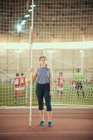 Pole vaulting - woman in purple shirt is standing with a long pole Reklamní fotografie