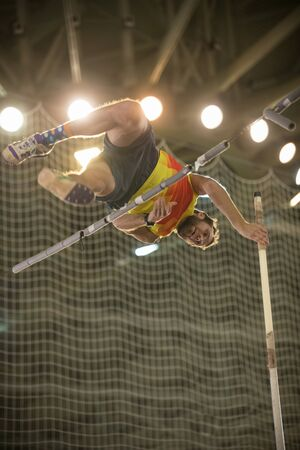 Pole vaulting - man is jumping over the bar and is going to let go of the pole