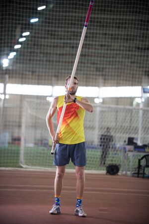 Pole vaulting - man in yellow shirt is standing with a pole in hands