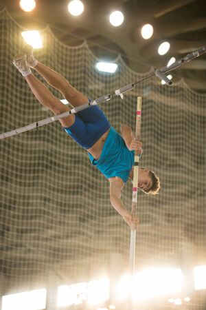 Pole vaulting - guy is jumping over the bar holding on to a pole