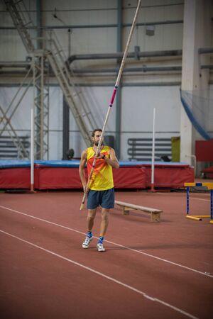 Pole vaulting - man is rising a long pole up Reklamní fotografie
