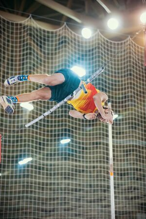 Pole vaulting - man is jumping over the bar in yellow t shirt