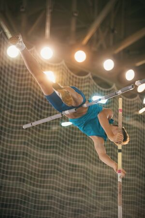 Pole vaulting - guy in blue t shirt is jumping over the bar holding on to a pole