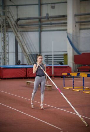 Pole vaulting - woman is holding a long pole in her hands