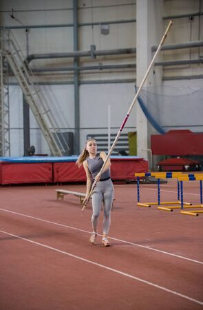 Pole vaulting - woman in gray shirt is going to run with a long pole in her hands