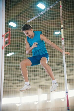 Pole vaulting - man is falling after a jump with a pole and smiling